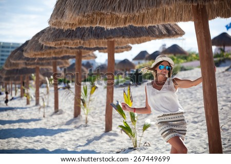 Beautiful tanned woman posing in sunshade under beach palapa, enjoying summer vacation - stock photo