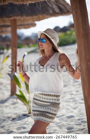 Beautiful tanned woman posing in sunshade under beach palapa, enjoying summer vacation - stock photo