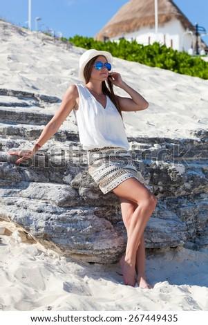 Beautiful tanned woman posing rock's background, enjoying summer vacation - stock photo