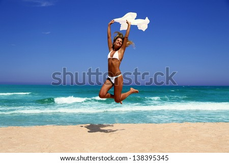 Beautiful tanned woman with a white sheet enjoying the sun on beach. - stock photo