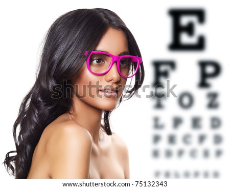 beautiful tanned woman with long curly hair wearing pink glasses on eye test background - stock photo