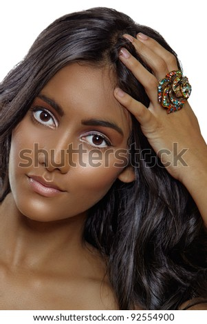 beautiful tanned woman with natural make-up and long curly hair wearing a large ring.