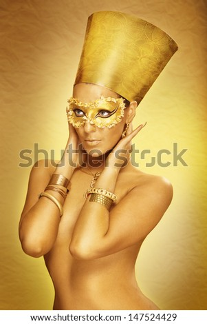 Beautiful tanned young woman on golden backround with golden facepaint stylized like Egyptian queen Nifertiti. profesionally retouched - stock photo