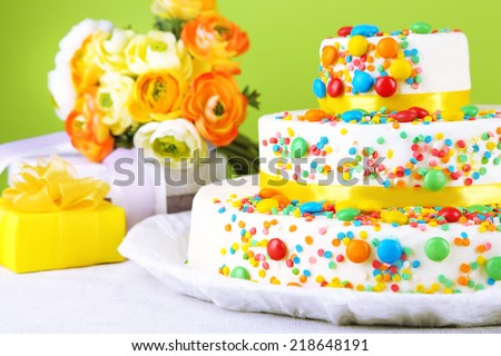Beautiful tasty birthday cake and gifts on color background - stock photo