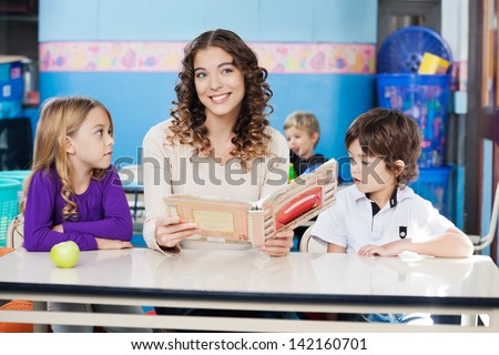 Beautiful teacher looking away while holding book with children at desk in classroom - stock photo