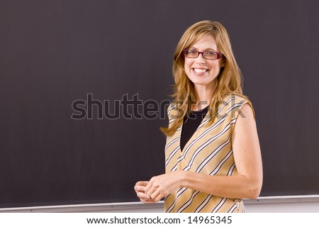 Beautiful teacher smiling from the front of the room with a blackboard behind her. - stock photo