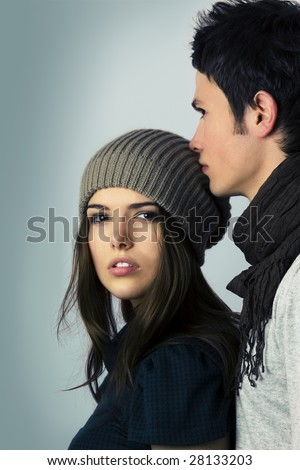 beautiful teen age girl looking at the camera and man kissing her on the head isolated on blue background