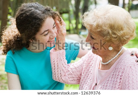 Beautiful teen girl and her loving grandmother smiling at each other. - stock photo