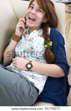 Beautiful teen girl at home with a mobilephone - stock photo