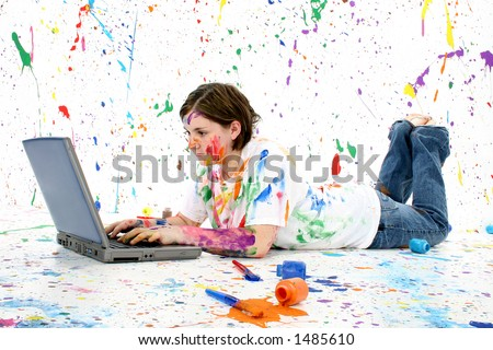 Beautiful teen girl covered in paint with laptop laying on floor - stock photo