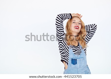 beautiful teen girl enjoying isolated on white background with copy space. Cheerful blond hair young woman in fashion striped and denim clothes posing in studio - stock photo
