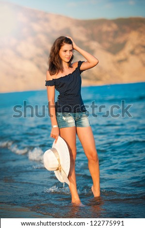 Beautiful teen girl goes on coast of ocean with straw hat in hands .Lady going on the beach with white hat