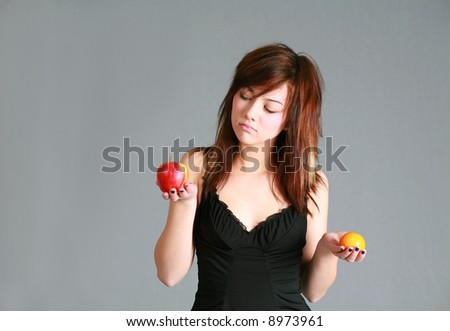 beautiful teen girl holding apple and orange