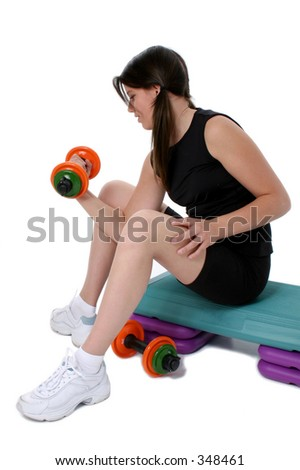 Beautiful Teen Girl Holding Colorful Weights while sitting on aerobic step.  Over white. - stock photo