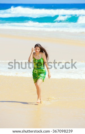 Beautiful teen girl in green dress walking along Hawaiian beach at water's edge - stock photo