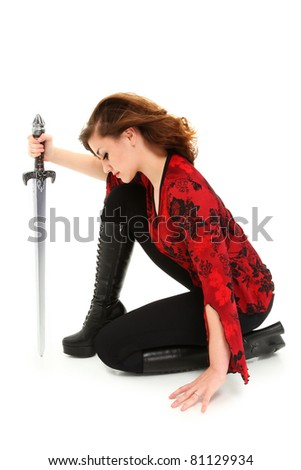 Beautiful teen girl on knees with sword over white background with clipping path. - stock photo