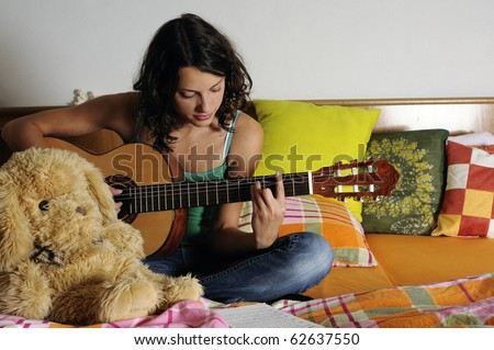 Beautiful teen girl playing guitar in her bedroom - stock photo