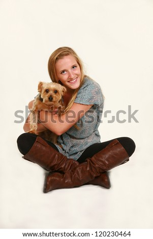 beautiful teen girl sitting and holding puppy in studio