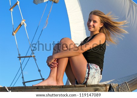 Beautiful teen girl sitting at stern of the ship - stock photo