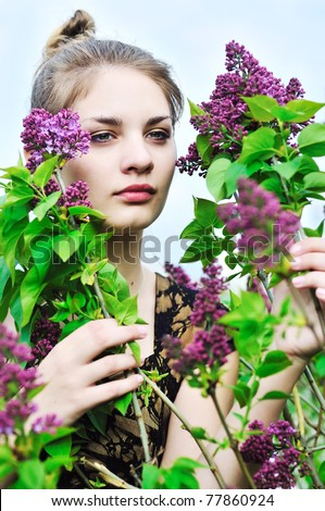 Beautiful teen girl smelling lilac blossoms - stock photo