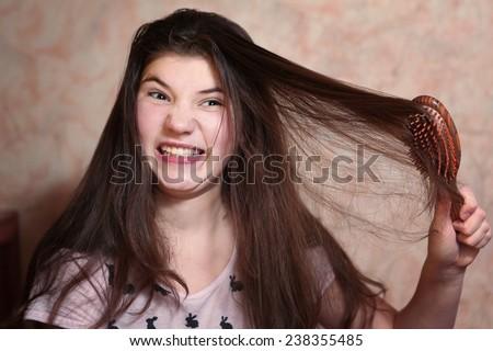 beautiful teen girl try comb her long dark thick hair - stock photo