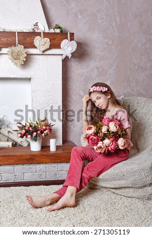 Beautiful teen girl with a bouquet of spring flowers in home interior. Barefoot girl sitting on a chair. The concept of a happy childhood. - stock photo