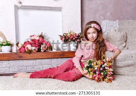Beautiful teen girl with a bouquet of spring flowers in home interior. Barefoot girl sitting on the floor. The concept of a happy childhood. - stock photo