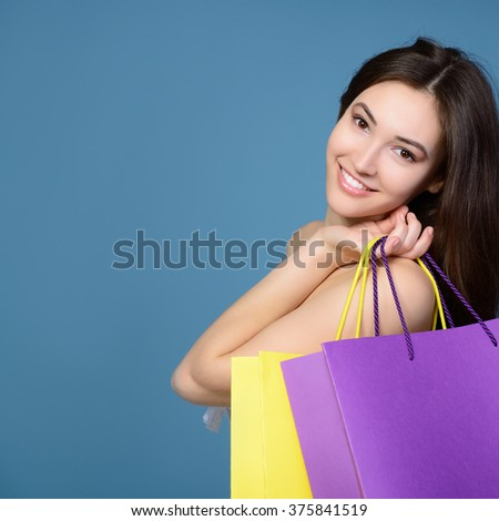 beautiful teen girl with colored sale shopping bags over blue background - stock photo