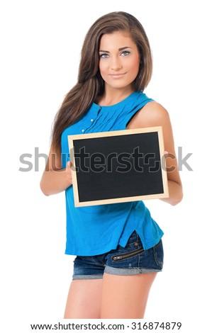 Beautiful teen girl with small blackboard posing on white background - stock photo