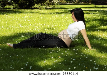 Beautiful teen pregnant woman relaxing in the park - stock photo