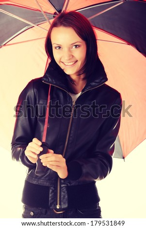 Beautiful teen woman dressed in black under red and black umbrella - stock photo