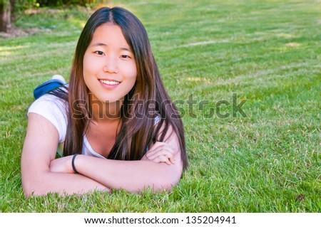 Beautiful Teenage Asian Girl lying on the grass.  Copy space. - stock photo