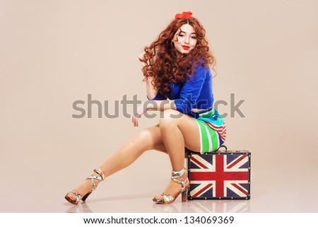 Beautiful teenage fashion model sitting on a suitcase - stock photo