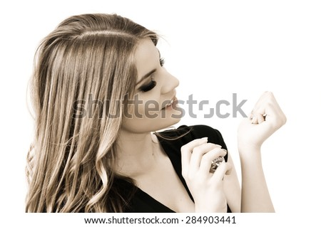 Beautiful teenage girl applying perfume on her hand, isolated on white - stock photo