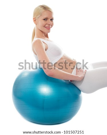 Beautiful teenage girl back stretch over exercise ball, looking at camera