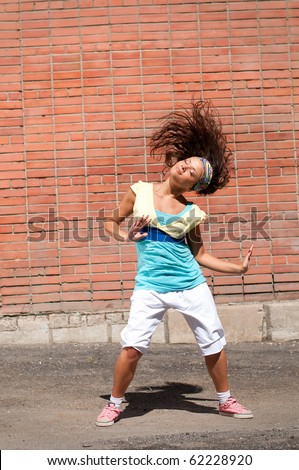 Beautiful teenage girl dancing hip-hop over red brick wall