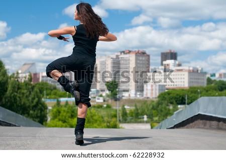 Beautiful teenage girl dancing hip-hop over urban city landscape - stock photo