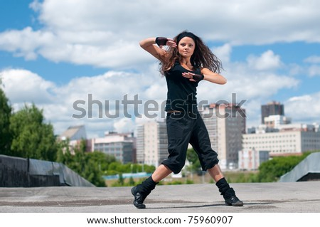 Beautiful teenage girl dancing in modern style over urban city landscape
