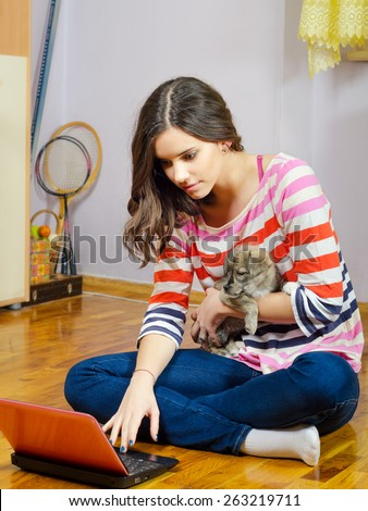 Beautiful teenage girl having fun in her room with notebook while holding small dog puppy - stock photo