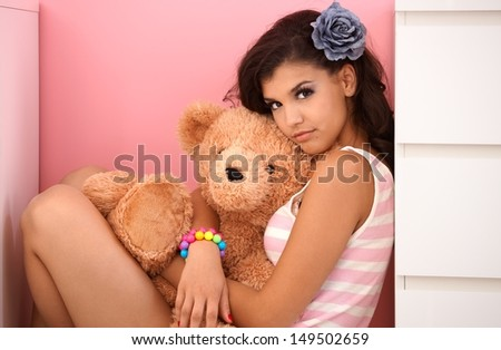 beautiful teenage girl hugging teddy bear, looking at camera. - stock photo