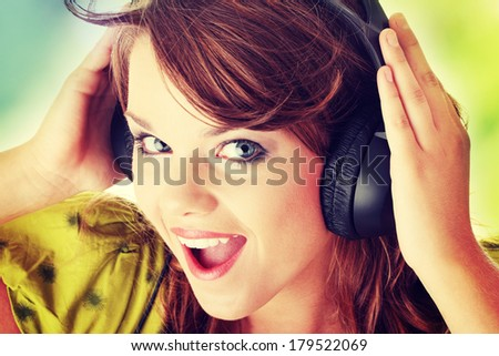 Beautiful teenage girl in a green dress listening to music with big headphones - stock photo