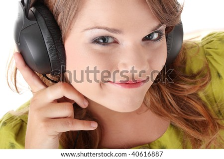 Beautiful teenage girl in a green dress listening to music with big headphones, isolated on white