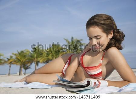 Beautiful teenage girl in bikini reading magazine lying on beach - stock photo