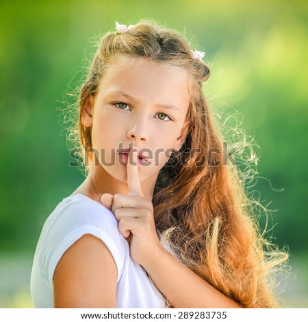 Beautiful teenage girl in white blouse raised index finger to her lips, against green of summer park. - stock photo