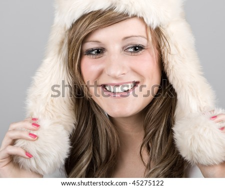Beautiful Teenage Girl in Winter Hat against Grey Background