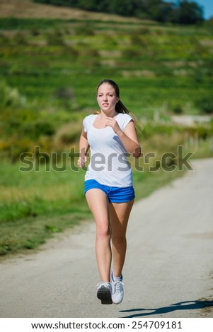 Beautiful teenage girl jogging in nature on sunny day - stock photo