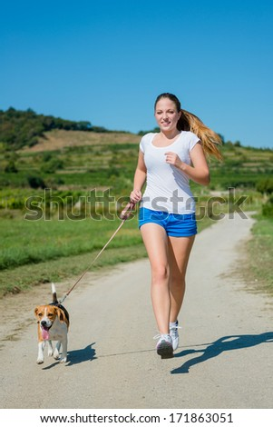 Beautiful teenage girl jogging with her pet (beagle dog) in nature - stock photo