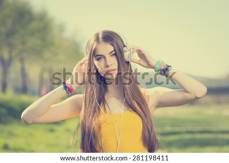 Beautiful teenage girl listening to music on headphones in park. Closeup of attractive young blonde Caucasian woman in yellow tank top with white headphones outdoors in summer. Color filter applied. - stock photo