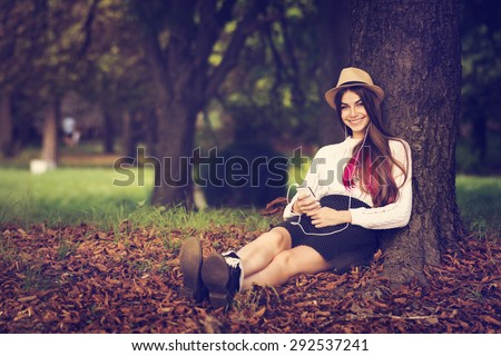 Beautiful teenage girl listening to music on smartphone sitting by the tree in park in autumn looking at camera smiling. Young woman with hat and pink hair portrait. Horizontal, retouched, filter. - stock photo