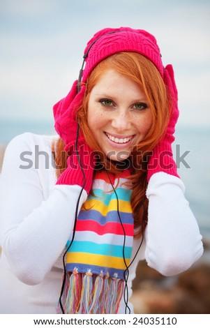 Beautiful teenage girl listening to music outdoors - stock photo